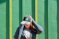 Положение шляпы shamrock молодой женщины нося перед зеленой стеной стоковое фото