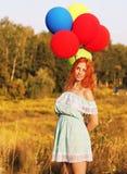 Положение redhead девушки с баллонами на желтых колосках стоковые изображения