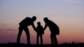 Положенные силуэты семьи вручают совместно, совершенные команда и поддержка, дело захода солнца акции видеоматериалы