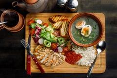 Положенный обедающий на супе таблицы, лука и яйца, рисе, куриной грудке стоковое изображение