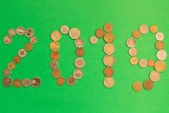 2019 положено из различных монеток на зеленую предпосылку Новый Yea стоковые фотографии rf