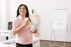 Положительная азиатская беременная женщина стоя в офисе Стоковые Фотографии RF