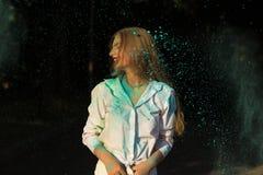 Положительная белокурая женщина в белой рубашке празднуя фестиваль i Holi Стоковые Фотографии RF