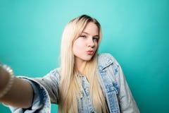 Положительная белокур-с волосами женщина принимая selfie на голубой предпосылке делая потеху с собой стоковая фотография