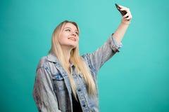 Положительная белокур-с волосами женщина принимая selfie на изолированной голубой предпосылке делая потеху с собой стоковая фотография rf