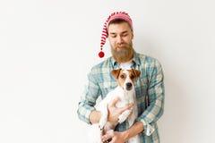 Положительная бородатая мужская модель носит праздничную шляпу и checkered рубашка, держит его любимый любимчика, над белизной стоковые фото