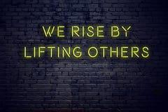 Положительная воодушевляя цитата на неоновой вывеске против кирпичной стены мы поднимаем путем поднимать другие иллюстрация штока