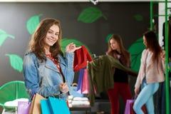 Положительная девушка держа пары красных ботинок в магазине Стоковые Изображения RF