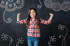 Положительная девушка усмехаясь и показывая симпатичный орнамент на стене Стоковые Фото