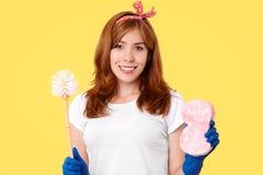 Положительная женская горничная идя очистить tooilet, носит вскользь белые футболку, держатель, щетку владениями и губку, предста стоковое изображение rf