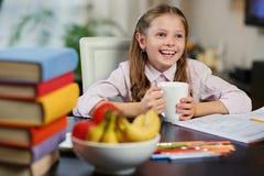 Положительная маленькая девочка выпивает чай утра Стоковые Изображения