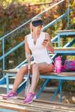 Положительная милая девушка говоря на телефоне после тренировки бадминтона на предпосылке стадиона Занятая концепция образа жизни Стоковое Изображение