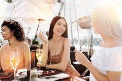 Положительная молодая женщина говоря к ее другу Стоковые Фотографии RF
