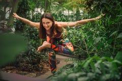 Положительная молодая женщина делая йогу работает для баланса на парнике Стоковое Изображение