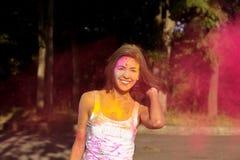 Положительная молодая женщина при короткие волосы представляя с взрывать Holi стоковые фотографии rf