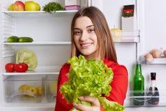 Положительная молодая привлекательная женщина держит салат, был vegeterian, стойки против раскрытого холодильника полного фрукта  Стоковое Изображение RF