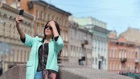 Положительная привлекательная женщина перемещения принимая selfie используя смартфон на исторической строя предпосылке видеоматериал