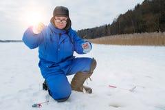 Положительная усмехаясь рыбная ловля старика на озере на холодном зимнем дне стоковые изображения rf