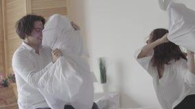 Положительное бой пар с подушками сидя на кровати Молодой супруг и жена имея потеху совместно Отдых счастливого видеоматериал