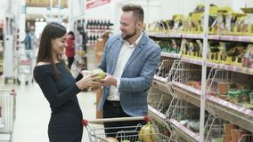 Положительное видео молодых пар, женщины делает смешную сторону с плодами на супермаркете сток-видео