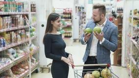 Положительное видео молодых пар, женщины делает смешную сторону с плодами на супермаркете видеоматериал