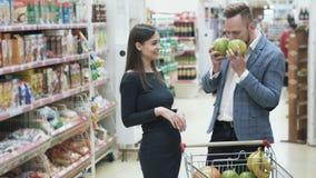 Положительное видео молодых пар, женщины делает смешную сторону с плодами на супермаркете акции видеоматериалы