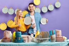 Положительное молодое внушительное белокурое ликование женщины на хороших результатах после мыть блюда стоковые фото