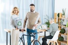 Положительные активисты eco усмехаясь пока стоящ с велосипедом и рециркулированной бумагой Стоковые Изображения RF