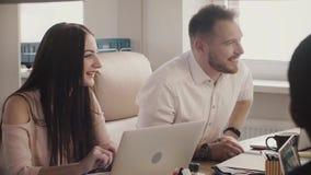 Положительные европейские бизнесмены проводят собеседование для приема на работу, беседу к персоне таблицей в современный светлый сток-видео