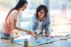 Положительные жизнерадостные женщины обсуждая их проект Стоковое Фото