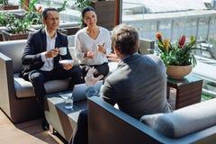 Положительные жизнерадостные коллеги встречая на обеде Стоковые Фото