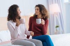 Положительные запомненные девушки выпивая чай и беседовать Стоковая Фотография RF