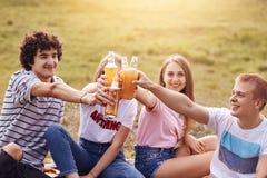 Положительные мальчики и девушки тратят свободное время внешнее, clink бутылки свежего сидра, имеют счастливые выражения, праздну стоковые изображения rf