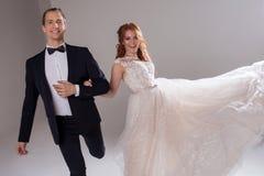 Положительные молодые пары смеясь над и танцуя совместно Пары в студии светлая предпосылка Стоковая Фотография