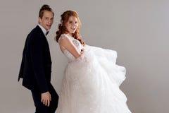 Положительные молодые пары смеясь над и танцуя совместно Пары в студии светлая предпосылка Стоковые Изображения