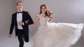 Положительные молодые пары смеясь над и танцуя совместно Пары в студии светлая предпосылка Стоковое Изображение RF
