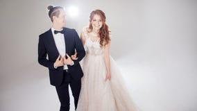 Положительные молодые пары смеясь над и танцуя совместно Пары в студии светлая предпосылка Стоковая Фотография RF