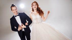Положительные молодые пары смеясь над и танцуя совместно Пары в студии светлая предпосылка Стоковое фото RF