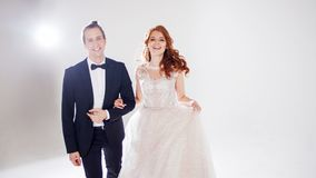 Положительные молодые пары смеясь над и танцуя совместно Пары в студии светлая предпосылка Стоковое Фото