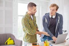 Положительные мужские коллеги изменяя отчет Стоковое Изображение RF