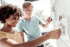 Положительные славные люди смотря whiteboard стоковые изображения rf