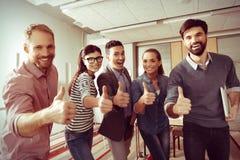 Положительные счастливые люди показывая большие пальцы руки вверх показывать Стоковые Изображения