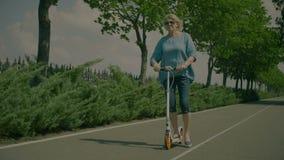 Положительный активный старший самокат катания женщины в парке видеоматериал