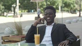 Положительный афро американский специалист по маркетингу в eyewear и вскользь обмундировании имея телефонный звонок в кафе акции видеоматериалы