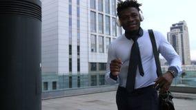 Положительный бизнесмен при наушники танцуя outdoors сток-видео