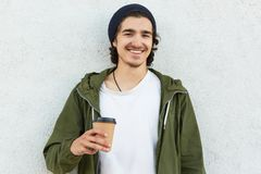 Положительный битник в стильном черном headgear, белая футболка и анорак, бумажный стаканчик владениями кофе, наслаждаются свобод стоковые фотографии rf