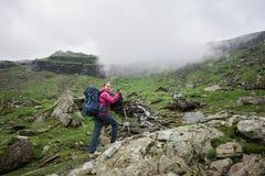 Положительный женский туристский взбираясь утес с идя ручками перед зелеными скалистыми лугами и горами в Румынии Стоковое Изображение