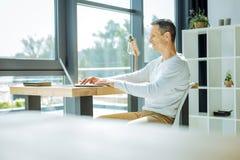Положительный жизнерадостный человек работая в его офисе Стоковая Фотография RF