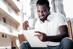 Положительный запомненный контракт чтения парня и выпивая кофе Стоковое Фото