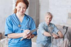 Положительный запомненный медицинский работник усмехаясь пока принимающ примечания Стоковое фото RF